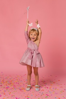 Fille heureuse en costume de fée avec des confettis