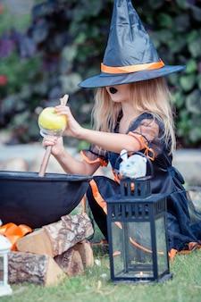 Fille heureuse en costume d'halloween avec citrouille jack.trick ou traiter