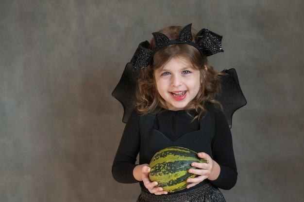 Fille heureuse en costume d'halloween avec petite citrouille verte sur un espace gris
