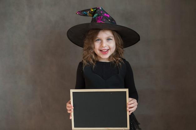 Fille heureuse en costume de sorcière halloween avec bureau noir dans les mains