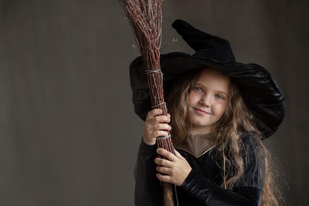 Fille heureuse en costume de sorcière halloween sur fond gris