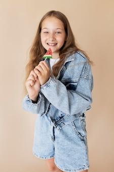 Fille heureuse de coup moyen posant avec de la crème glacée