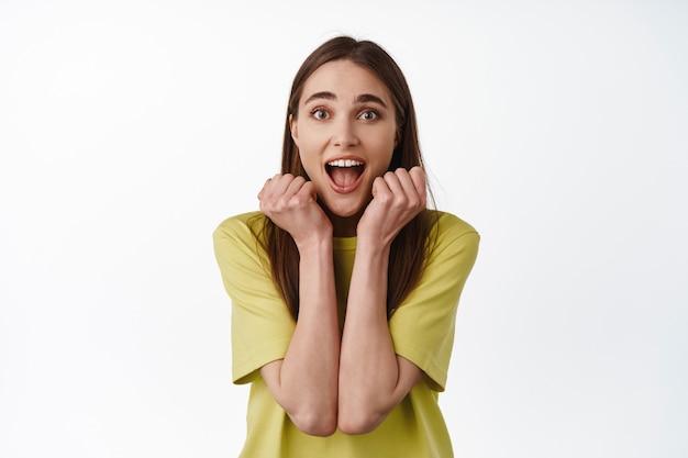 Une fille heureuse crie et regarde avec joie, vérifiant les grandes nouvelles géniales debout sur le blanc.