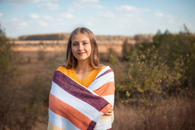 Fille heureuse dans le champ d'automne enveloppé de plaid à la recherche de l'appareil photo