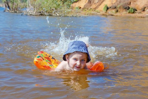 Fille heureuse dans un chapeau joue dans l'eau et éclabousse