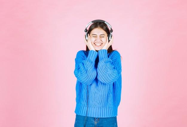 Fille heureuse dans les écouteurs debout sur le rose.