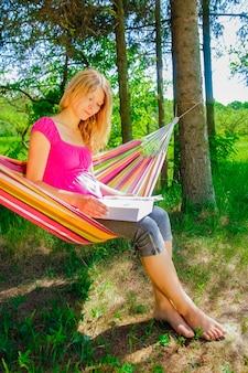 Fille heureuse dans un hamac lisant un livre sur la nature dans le parc