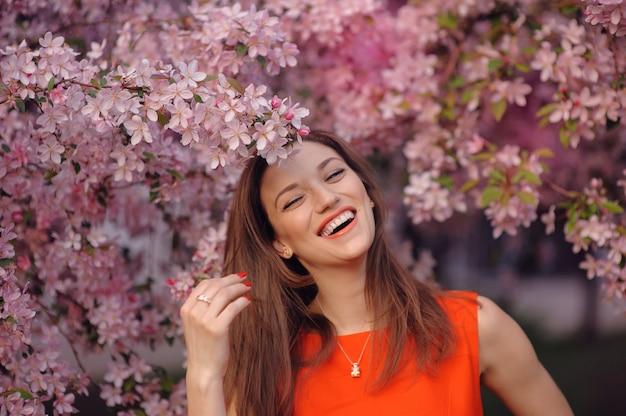 Fille heureuse dans le parc fleuri de printemps