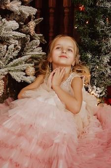 Fille heureuse dans une robe rose près de l'arbre de noël