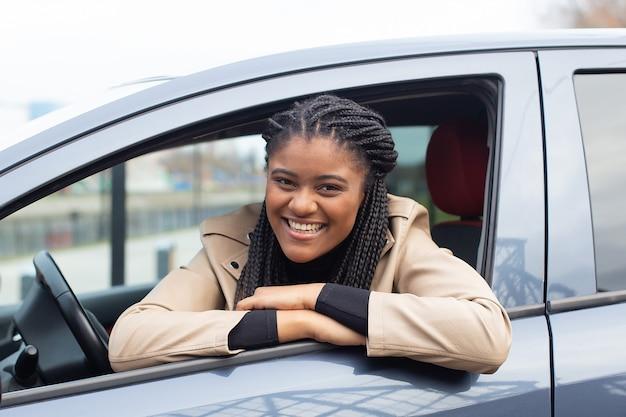 La fille heureuse dans une voiture au volant, afro-américain