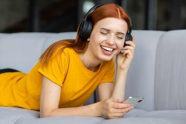 Fille heureuse avec des écouteurs et des cheveux rouges écoutant des chansons préférées ou une mélodie sur un téléphone portable allongé sur le canapé à la maison, souriant. concept de détente à la maison