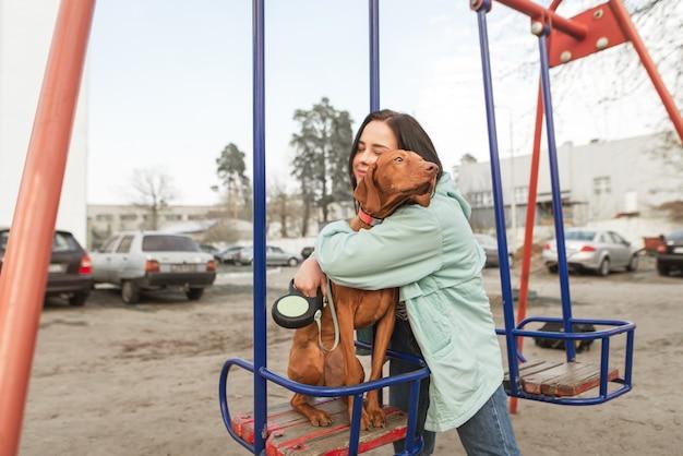Fille heureuse embrasse un beau jeune chien assis sur une balançoire.