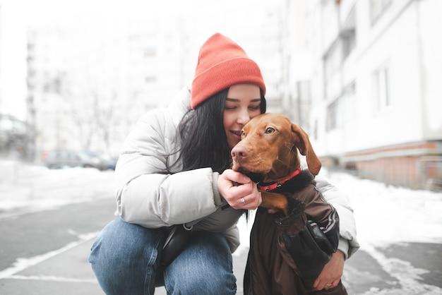 Fille heureuse embrasse et embrasse un beau chien orange