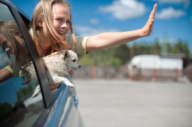 Fille heureuse d'enfant et chihuahua de chien regardant par la fenêtre ouverte de voiture