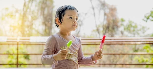 La fille heureuse d'enfant dans une chemise mouillée mangeant du popsicle de crème glacée dans le fond extérieur naturel.