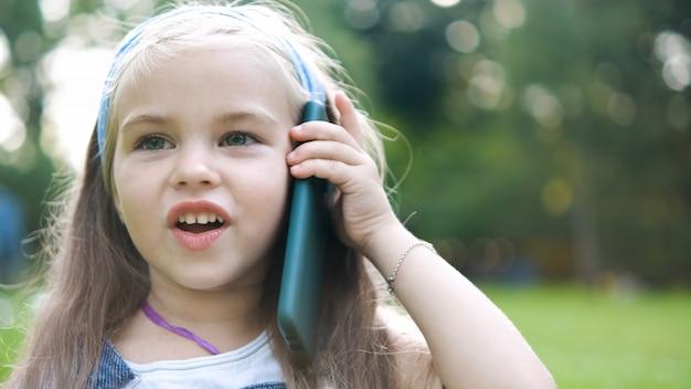Fille heureuse d'enfant parlant au téléphone portable dans le parc d'été.