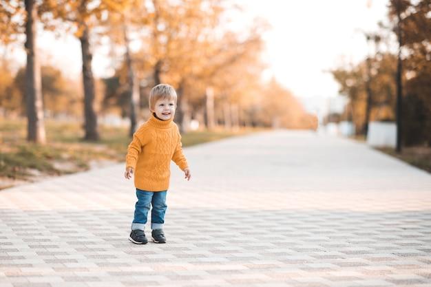 Fille heureuse d'enfant portant le chandail tricoté jaune jouant dans le parc