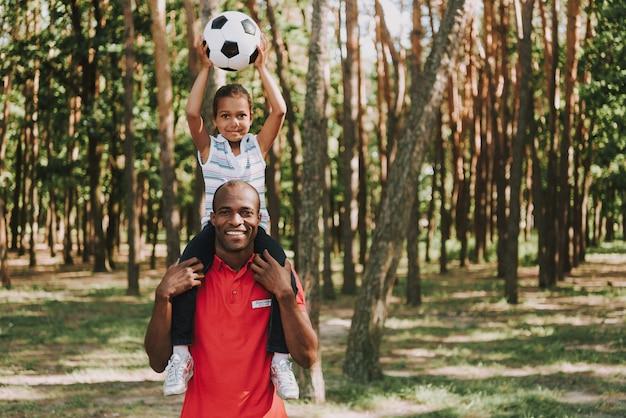 Fille heureuse avec l'épée de papa sur le cou en forêt,