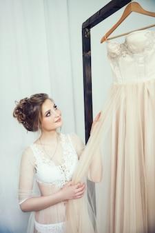 Fille heureuse essayant sa robe de mariée. jours fériés et événements