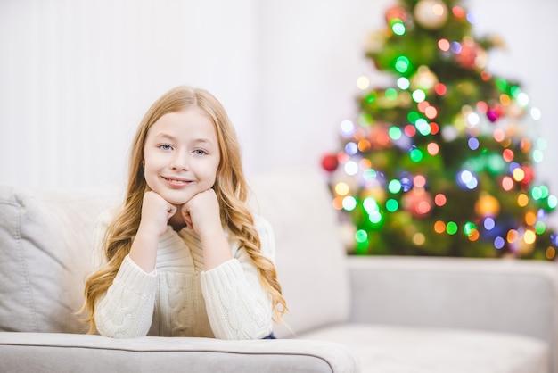 La fille heureuse était allongée sur le canapé près du sapin de noël