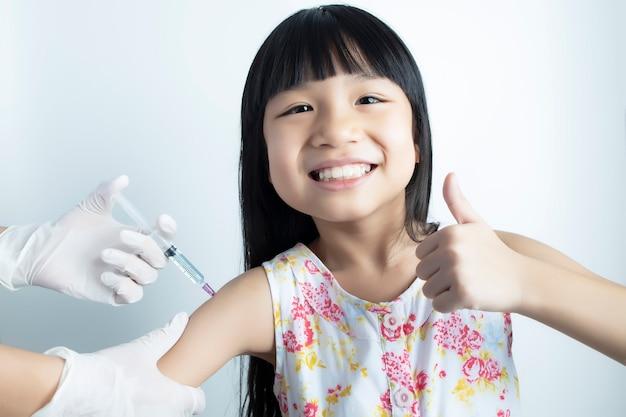 Fille heureuse d'être vaccinée pour le traitement et la prévention par un médecin ou une infirmière avec un mur blanc