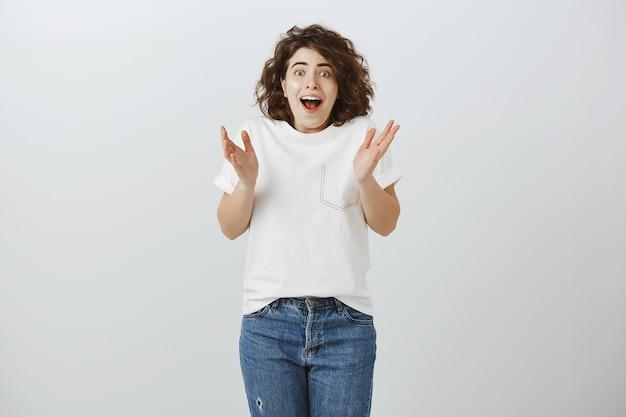 Une fille heureuse excitée entend des nouvelles incroyables, tape des mains et a l'air joyeuse