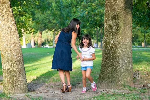 Fille heureuse excitée jouant à des jeux actifs avec sa mère à l'extérieur, debout près des arbres dans le parc et riant. toute la longueur. concept d'activités et de loisirs de plein air en famille