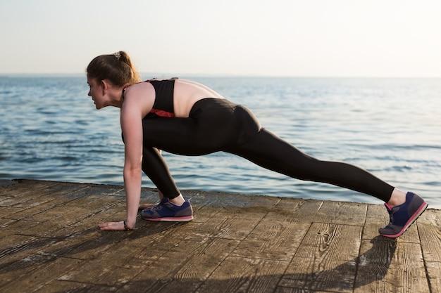 La fille heureuse exécute des exercices de sport sur la côte de mer