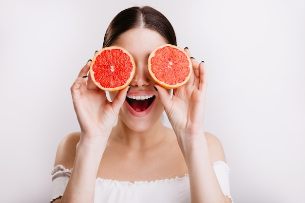 Fille heureuse avec une expression faciale émotionnelle positive couvre ses yeux d'oranges, posant sur un mur isolé.