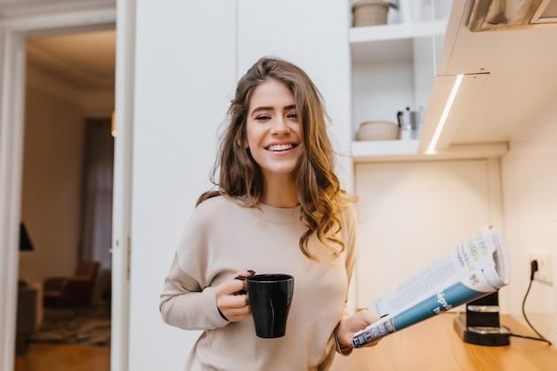 Fille heureuse exprimant le bonheur, buvant du café dans sa cuisine confortable