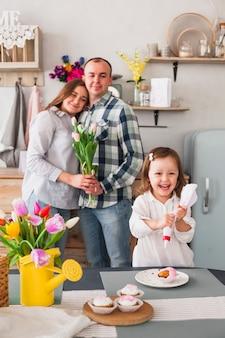 Fille heureuse, faire des petits gâteaux près des parents avec des fleurs