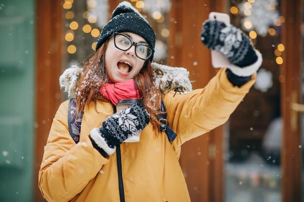Fille heureuse fait un selfie dans la ville d'hiver. fille fait selfie en hiver et rue gelée