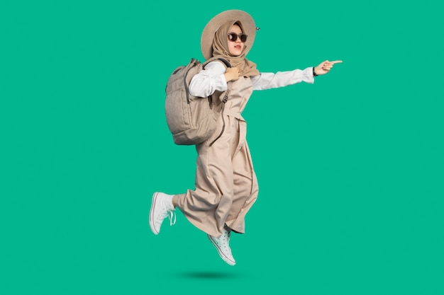 Fille heureuse de femme avec le sac et les verres sautent sur le fond de couleur verte