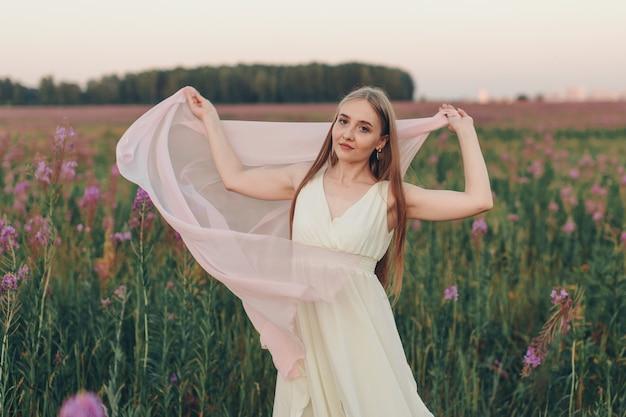 Une fille heureuse avec un foulard blanc se promène dans une prairie fleurie. amour et floraison printanière