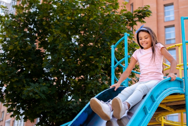 Fille heureuse, glisse sur un toboggan dans une aire de jeux