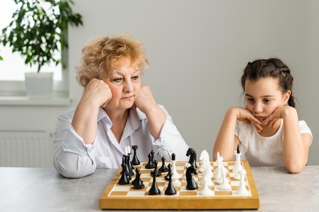 Fille heureuse avec grand-mère assise à la table et jouant aux échecs.