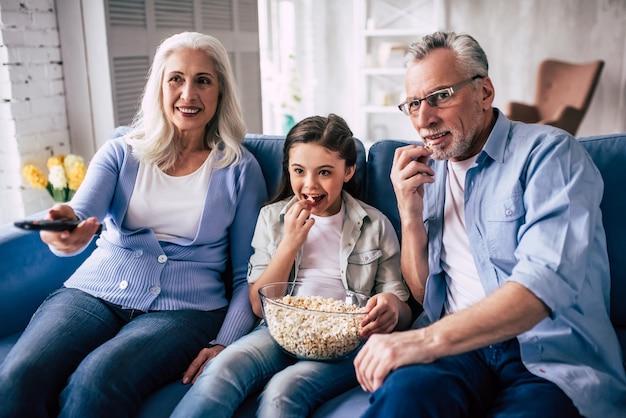 La fille heureuse et un grand-père regardant la télévision avec un pop-corn
