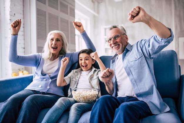 La fille heureuse et les grands-parents qui regardent la télévision et font des gestes