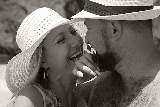 Fille heureuse et homme en chapeaux de plage se bouchent
