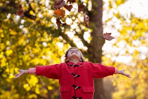 Fille heureuse, jetant les feuilles d'automne