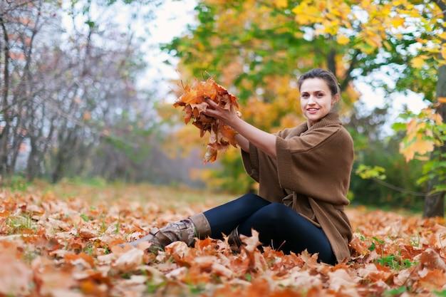 Une fille heureuse jette des érables
