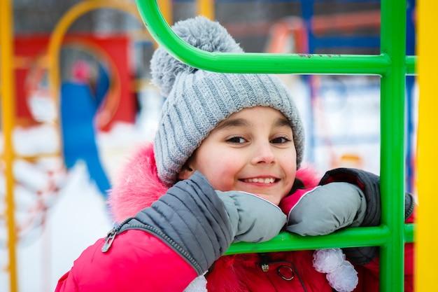 Fille heureuse jouant sur une aire de jeux à la journée glaciale d'hiver.
