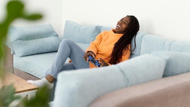 Fille heureuse jouant au jeu vidéo sur le canapé