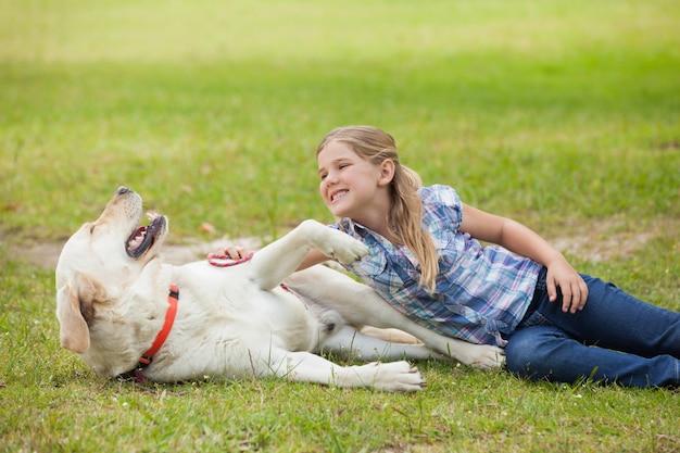 Fille heureuse jouant avec chien dans le parc