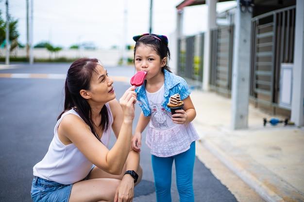 Fille heureuse jouant et mangeant la crème glacée avec la mère extérieure
