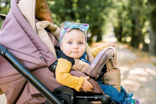 Fille heureuse en landau jouant dans la poussette sur fond nature. portrait mignon petite belle fille de 9 mois assis ou poussette et attendant maman.