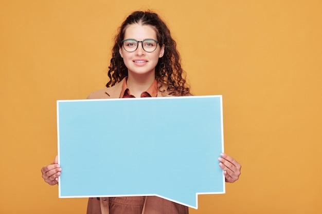 Fille heureuse avec de longs cheveux ondulés foncés tenant une affiche vierge carrée avec fond pour votre annonce