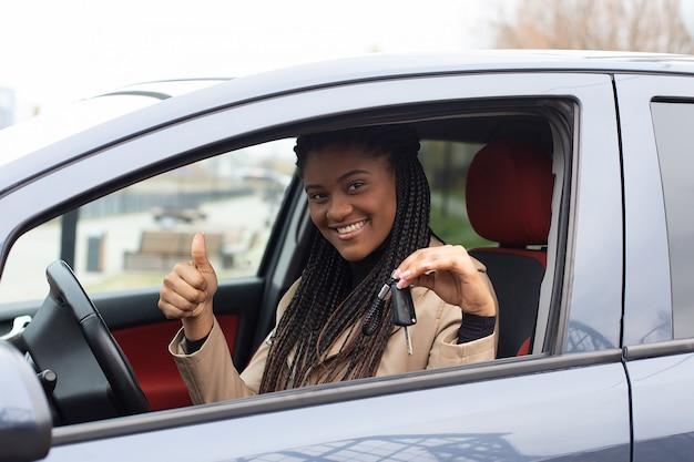 La fille heureuse a loué une voiture, afro-américaine