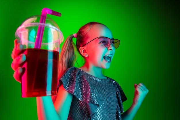 Fille heureuse avec des lunettes de soleil tenant du jus
