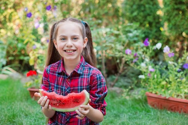 Fille heureuse mangeant de la pastèque dans le jardin. les enfants mangent des fruits à l'extérieur. collation saine pour les enfants. petite fille jouant dans le jardin en mordant une tranche de melon d'eau.